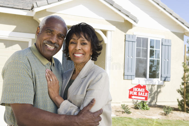 Couples en Front Of Home For Sale images stock