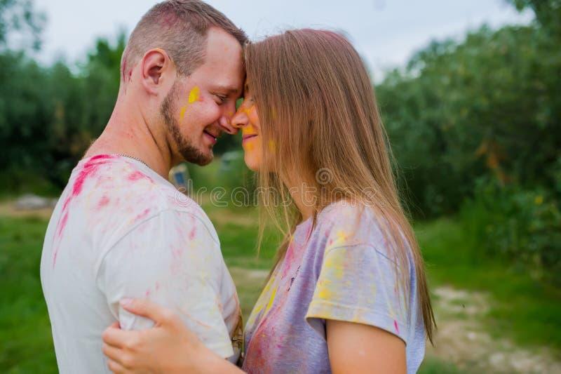 Couples en peintures multicolores étreignant dans le pré d'été Vue de c?t? image libre de droits