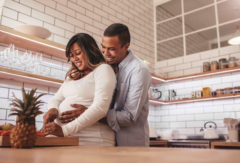 Couples enceintes faisant cuire la nourriture ensemble à la maison photographie stock libre de droits