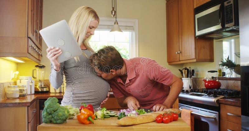 Couples enceintes mignons faisant cuire dans la cuisine image libre de droits