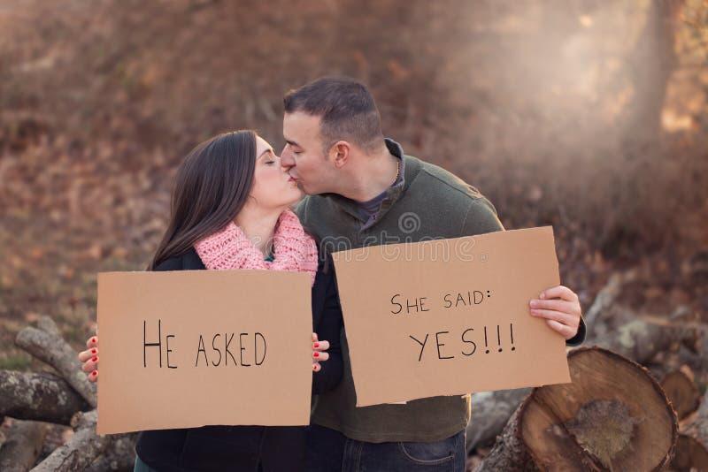 Couples engagés embrassant et tenant des signes de carton photo stock
