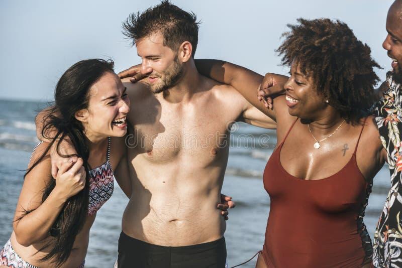 Couples enjoying together on beach stock image