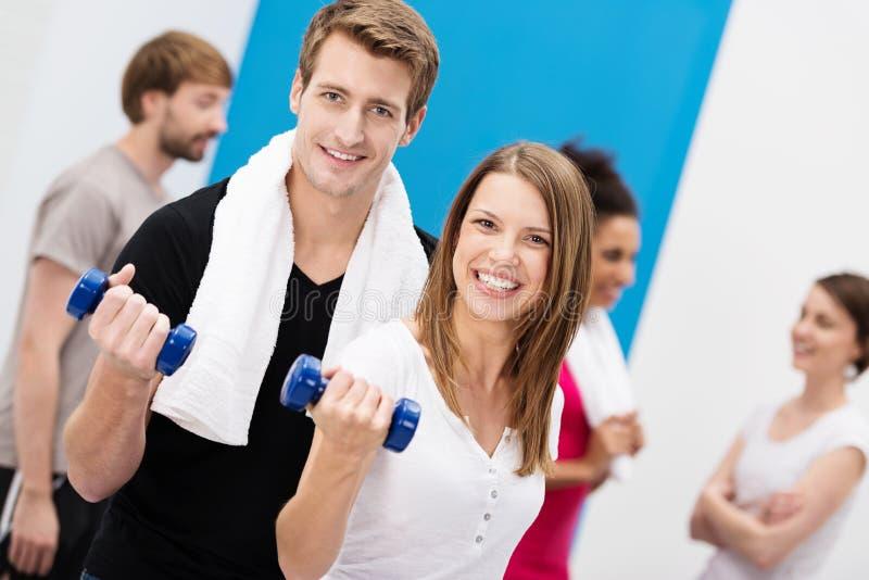 Couples enthousiastes établissant avec des haltères photo stock