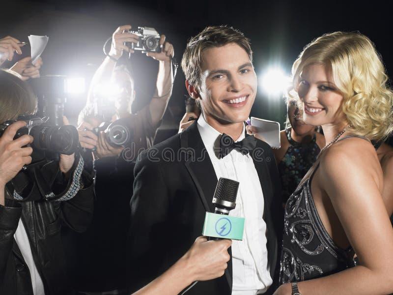 Couples entourés par des paparazzi image libre de droits