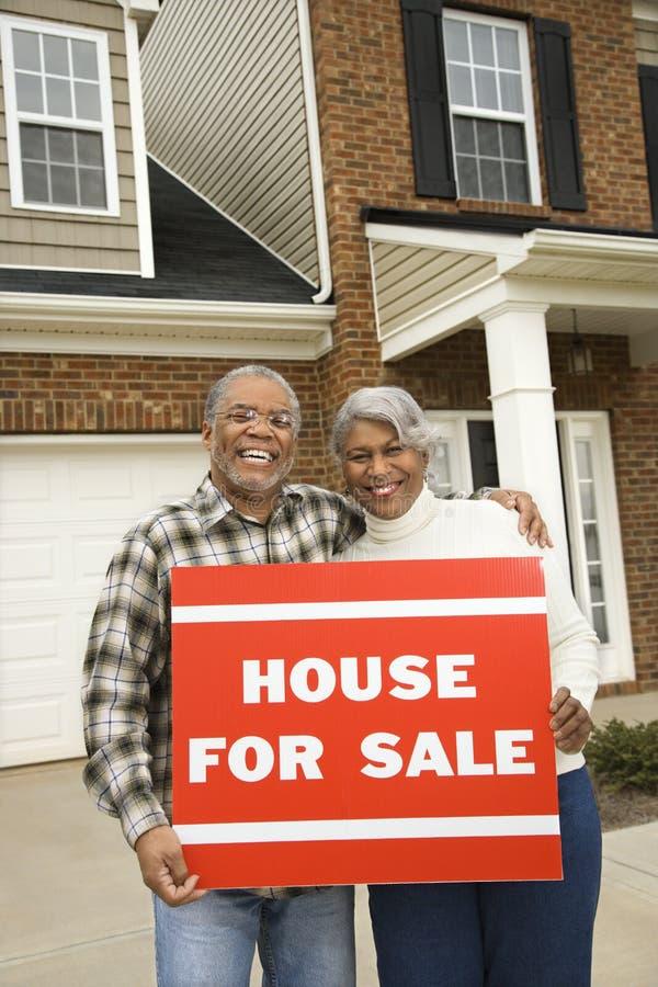 Couples entre deux âges retenant a à vendre le signe. photos stock