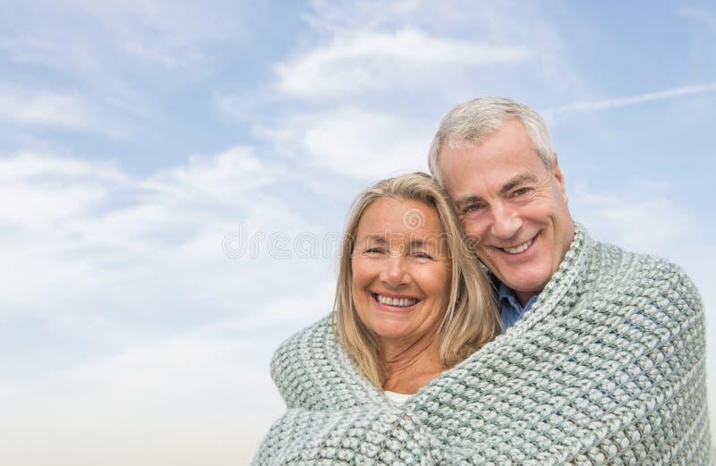 Couples enveloppés dans la couverture contre le ciel nuageux photo stock