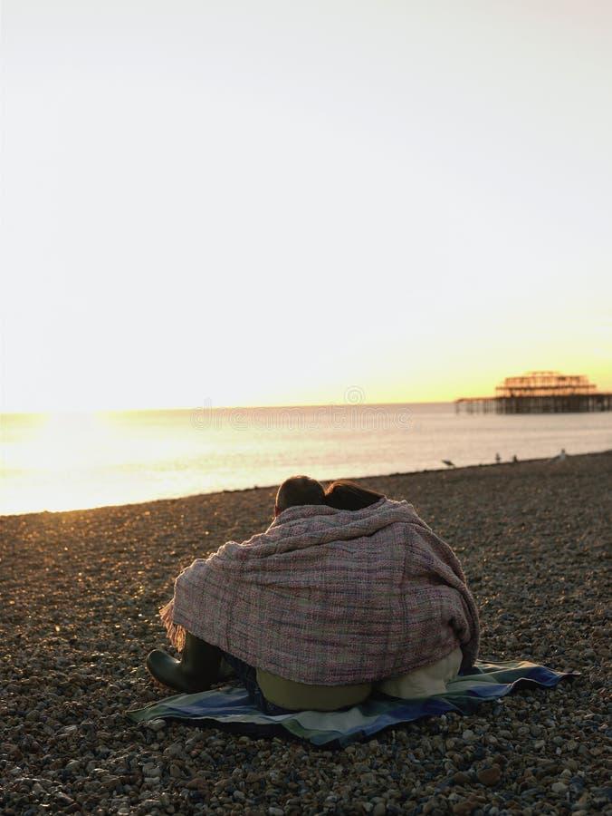 Couples enveloppés dans la couverture sur la plage au coucher du soleil  images libres de droits