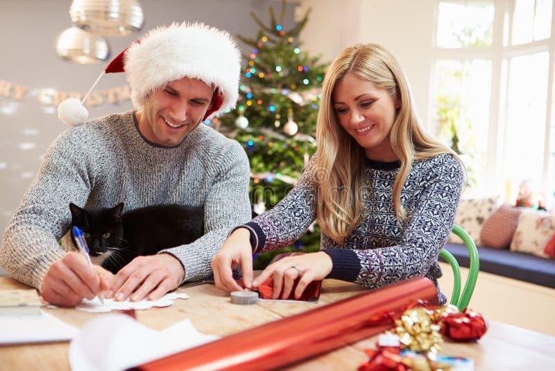 Couples enveloppant des cadeaux de Noël à la maison images stock