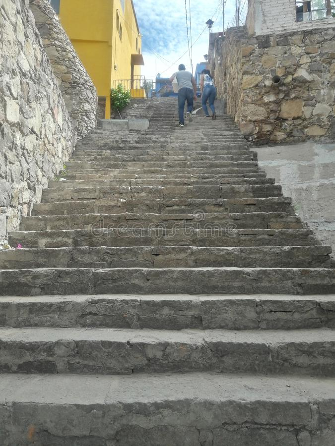 Couples escaladant Grey Staircase rustique en pierre antique et vieux le mur texturisé rustique symbolisant le défi et le progrès photos libres de droits