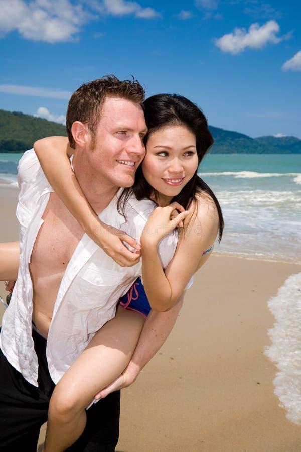 Couples espiègles au lo de plage photographie stock