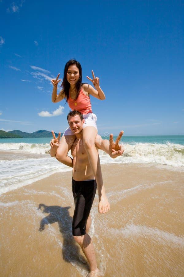 Couples espiègles par la plage photographie stock