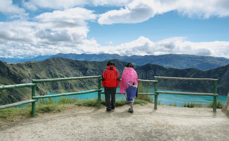 Couples ethniques équatoriens regardant la vue de la lagune majestueuse dans la caldeira de Quilotoa dans Quilotoa, Equateur photographie stock libre de droits