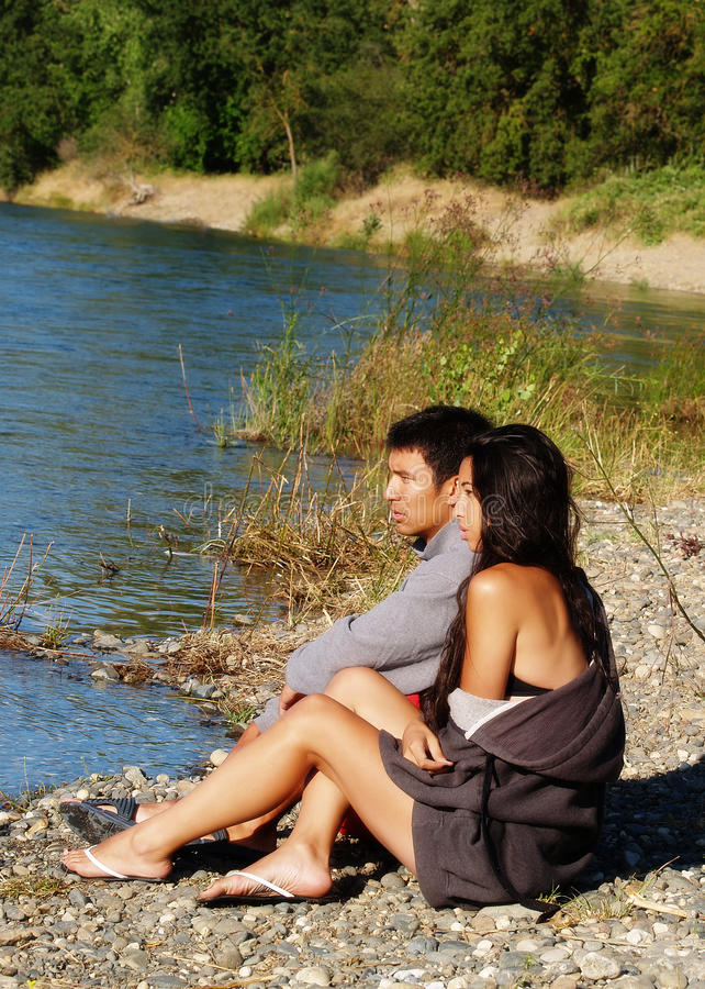 Couples ethniques se reposant dehors sur la berge photo libre de droits