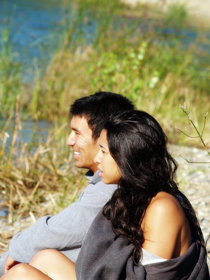 Couples ethniques se reposant dehors sur la berge image libre de droits
