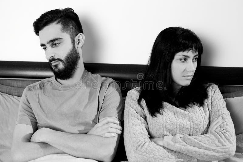 Couples fâchés dans le lit ne parlant pas entre eux images stock