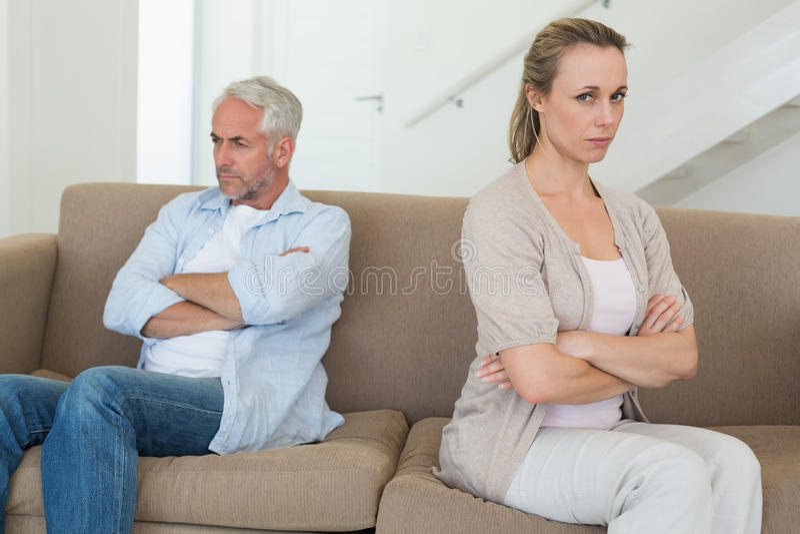 Couples fâchés se reposant sur le divan ne parlant pas entre eux images libres de droits