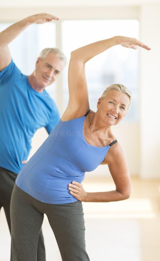 Couples faisant étirant l'exercice à la maison image libre de droits
