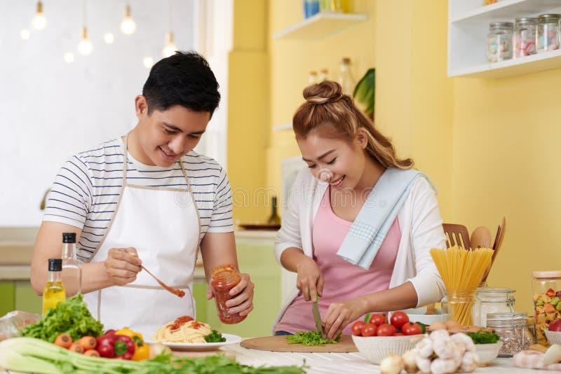 Couples faisant cuire les spaghetti et la salade photos libres de droits