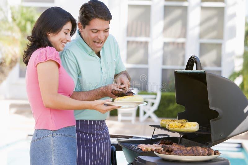 Couples faisant cuire sur un barbecue photos stock
