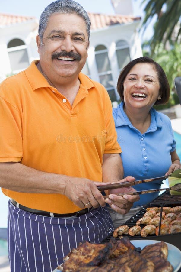 Couples faisant cuire sur un barbecue image libre de droits