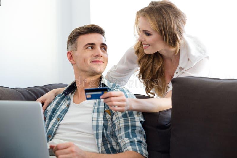 Couples faisant des achats dans l'Internet utilisant l'ordinateur portable et la carte de crédit photographie stock