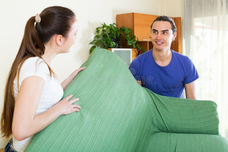 Couples faisant la relocalisation des meubles photos stock