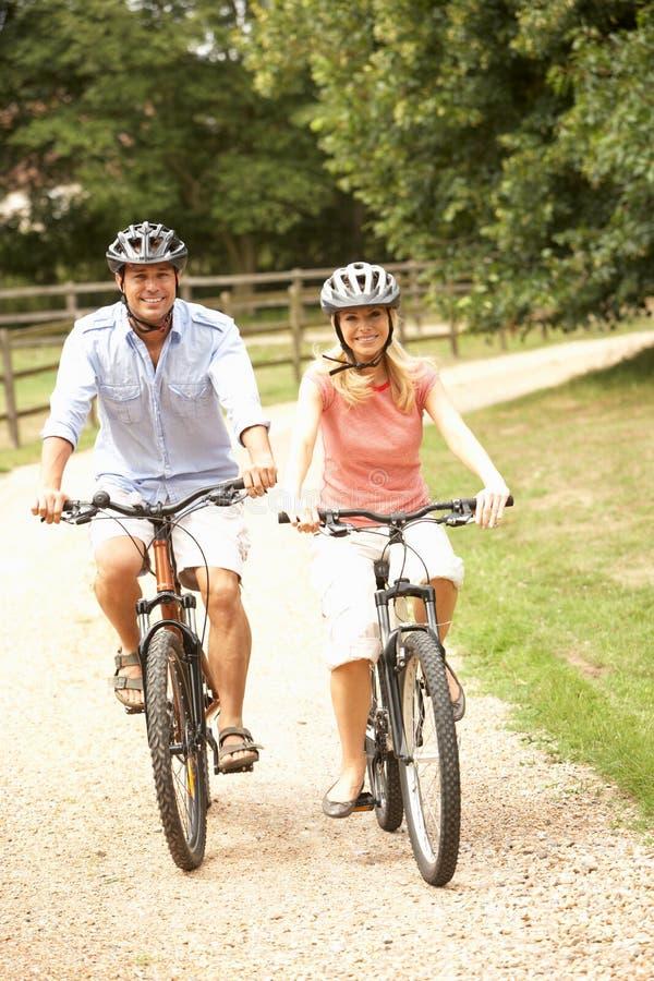 Couples faisant un cycle dans la sécurité s'usante Helme de campagne photo stock