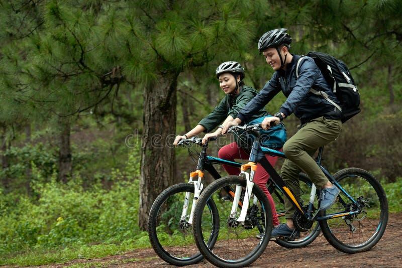 Couples faisant un cycle par la forêt photos libres de droits