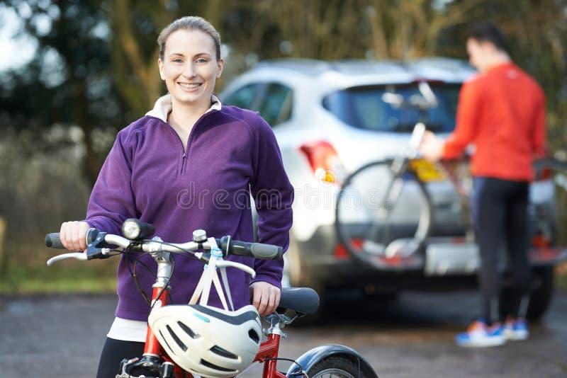 Couples faisant un cycle prenant des vélos de montagne de support sur la voiture images libres de droits