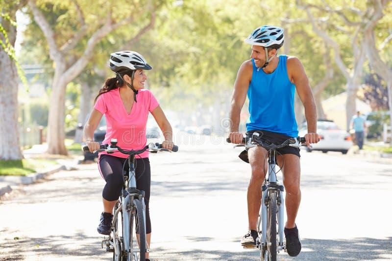 Couples faisant un cycle sur la rue suburbaine photographie stock libre de droits