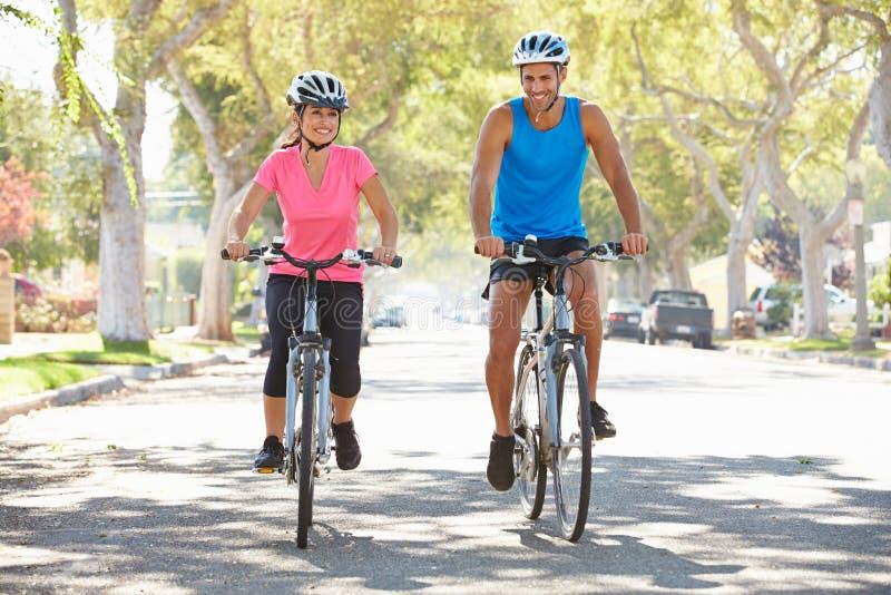 Couples faisant un cycle sur la rue suburbaine images libres de droits