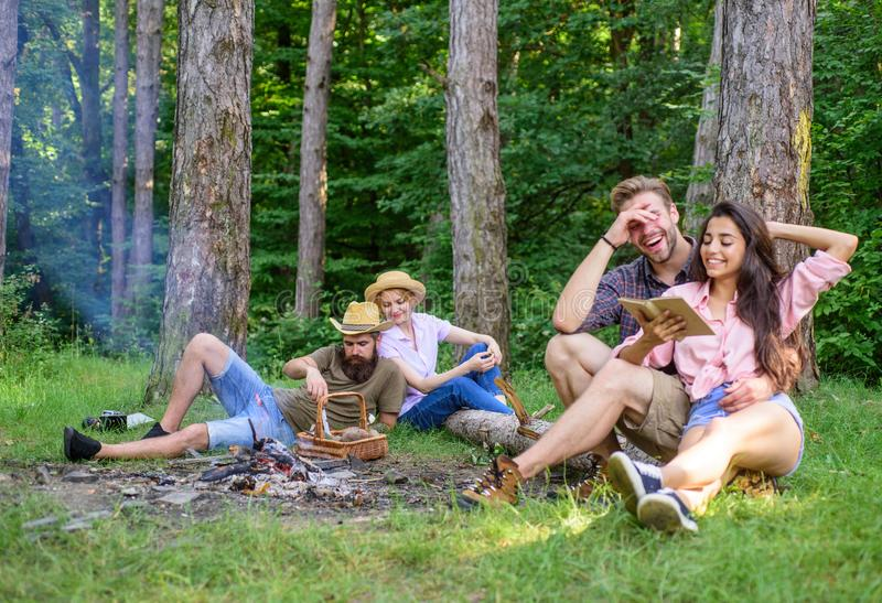 Couples or families having great time relaxing near campfire. Couples spend time outdoors on sunny day. Youth on picnic. Or hike relaxing and having fun stock photography