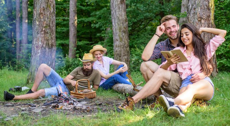 Couples or families having great time relaxing near campfire. Couples spend time outdoors on sunny day. Pleasant weekend. Youth on picnic or hike relaxing and royalty free stock photos