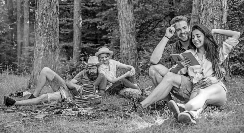 Couples or families having great time relaxing near campfire. Couples spend time outdoors on sunny day. Pleasant weekend. Youth on picnic or hike relaxing and stock photography