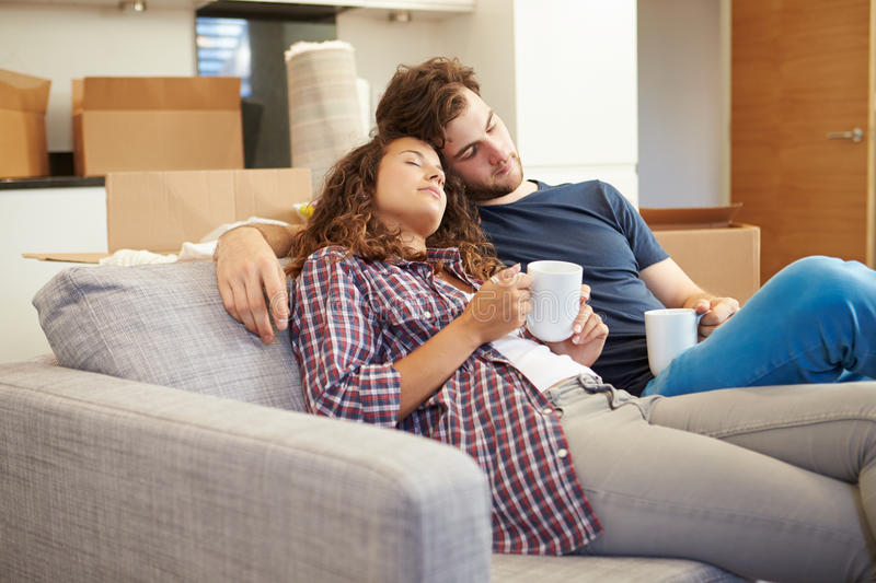 Couples fatigués détendant sur Sofa In New Home photos libres de droits