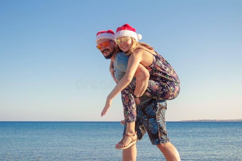 Couples ferroutant dans des chapeaux et des lunettes de soleil de Noël à la plage de la mer image libre de droits