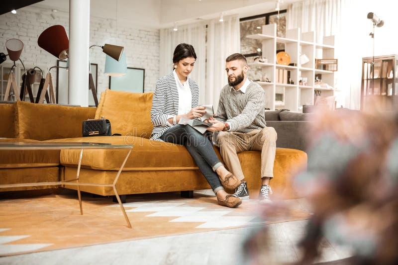 Couples focalisés occupés se reposant sur le divan brun de velours photo libre de droits