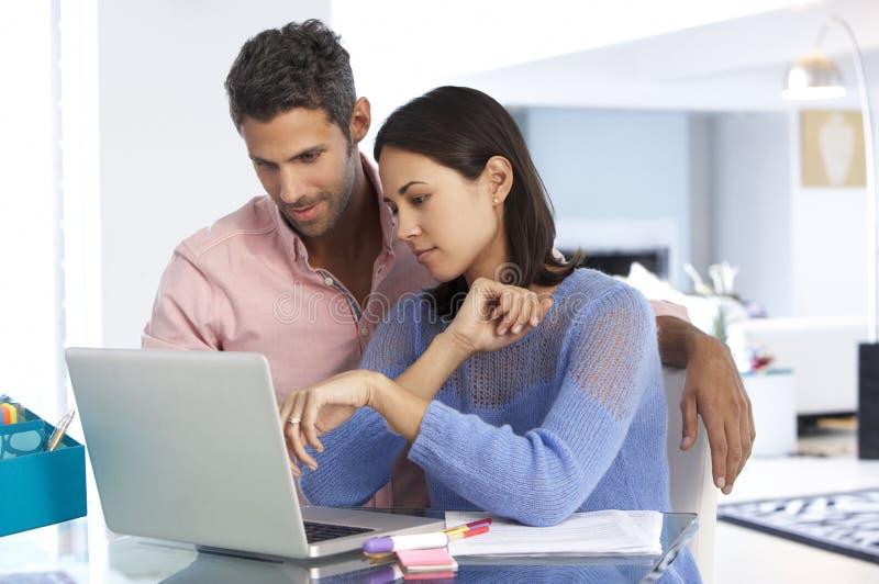 Couples fonctionnant à l'ordinateur portable dans le siège social photo stock