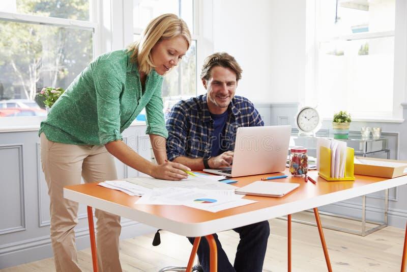 Couples fonctionnant ensemble au bureau dans le siège social photos stock