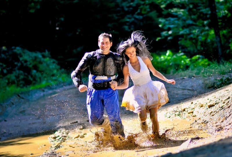 Couples fonctionnant par la boue images stock