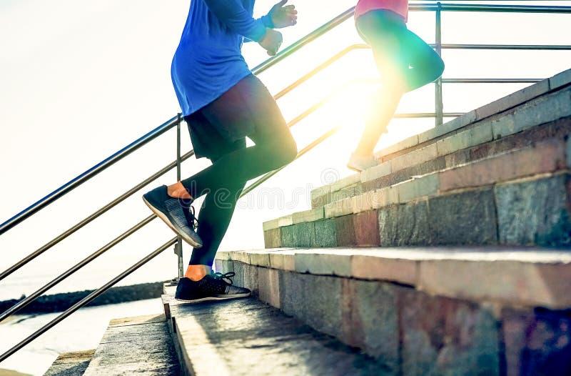 Couples fonctionnant sur des escaliers au coucher du soleil - amis faisant une session de séance d'entraînement s'exerçant pour o images stock