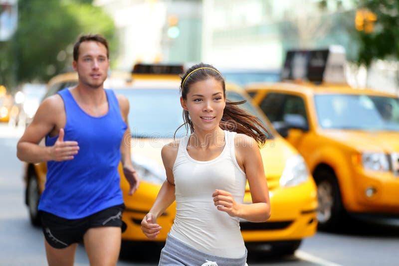 Couples fonctionnant sur la Cinquième Avenue, New York NYC image stock