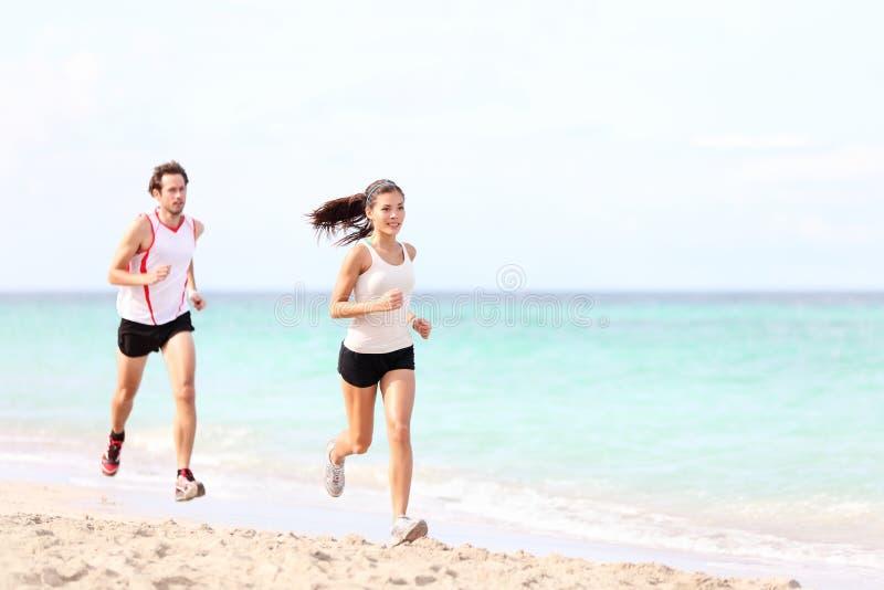 Couples fonctionnant sur la plage images stock