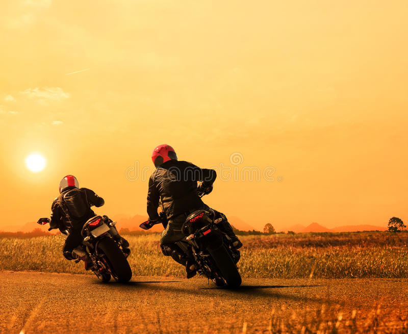 Couples friend motorcycle rider biking on asphalt highway against beautiful sun set sky use for people and man leisure activities. In motorsport and traveling stock photo