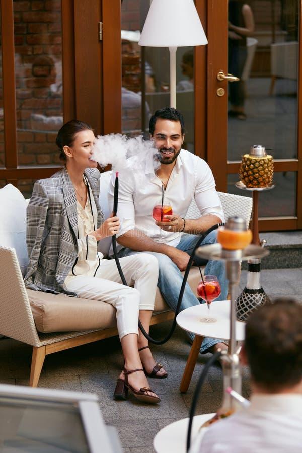 Couples fumant Shisha et buvant des cocktails dans la barre de narguilé photographie stock libre de droits