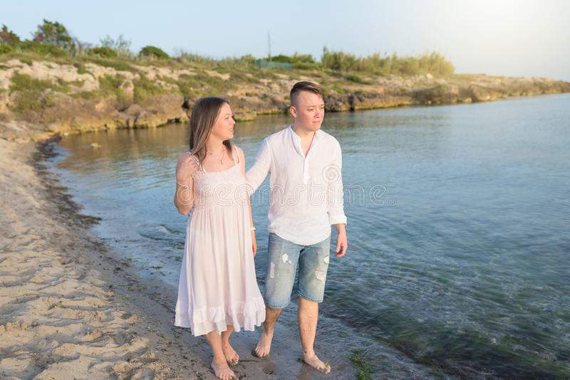 Couples ?g?s par milieu romantique heureux appr?ciant la belle promenade de coucher du soleil sur la plage photographie stock
