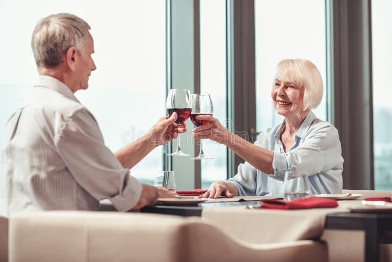 Couples gais buvant d'un bon vin dans un restaurant photo stock
