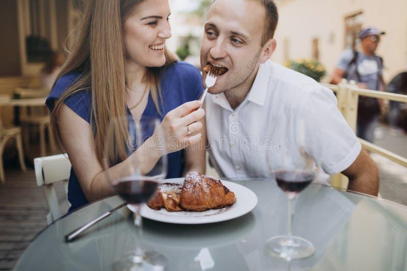 Couples gais dans un restaurant avec des verres de vin rouge jeune images libres de droits