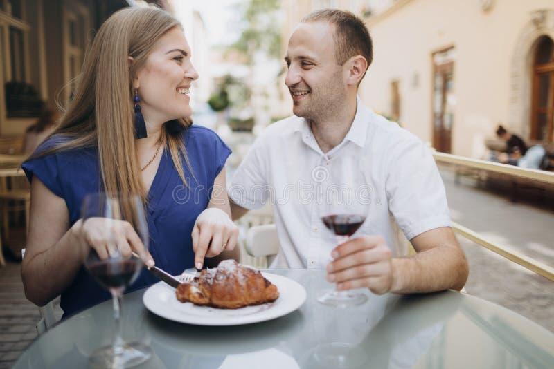Couples gais dans un restaurant avec des verres de vin rouge jeune photos libres de droits