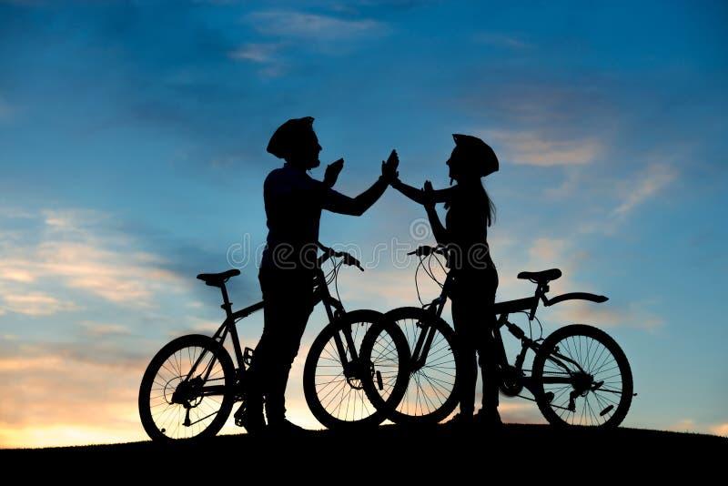 Couples gais des cyclistes battant des mains au coucher du soleil photo stock